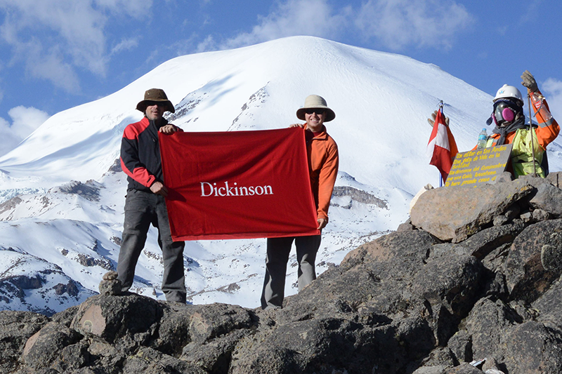 Professor of Earth Sciences Ben Edwards (left) and Will Kochtitzky '16 hold a Dickinson flag in front of a glacierized volcano in Peru, where they conducted fieldwork in 2015. Kochtitzky recently presented original research arising from that work.