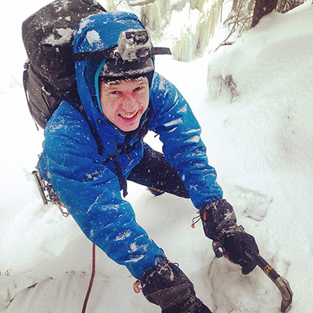 sam kilburn climbs up an icy mountain.