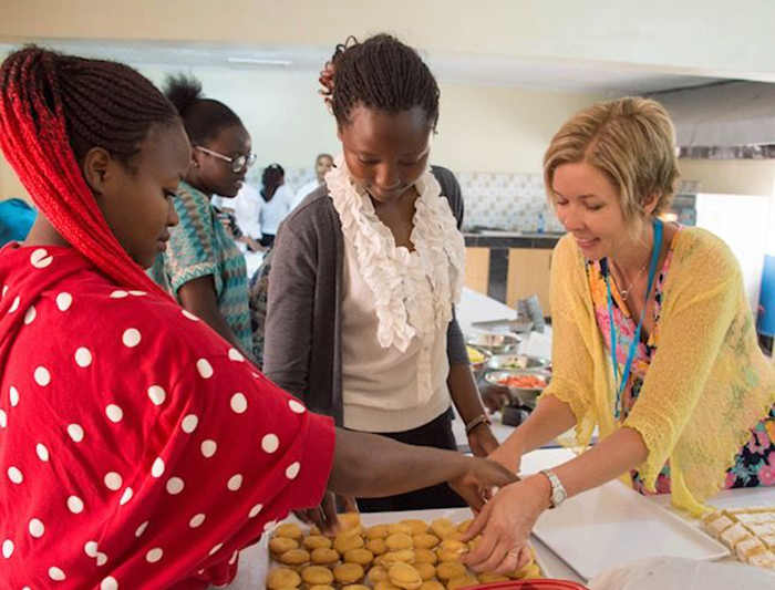 Jill Graby Shuck '93 leads a baking demonstration during the official launch of a baking program in Kenya. Led by a faith-based nonprofit, the program help adult students gain confidence and agency through community and by learning a marketable skill.