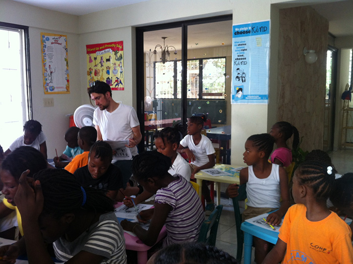 Christopher Brokus '15 works with children on their oral-language skills. Photo by Dominique Pierre, program director of Children of Haiti Project.