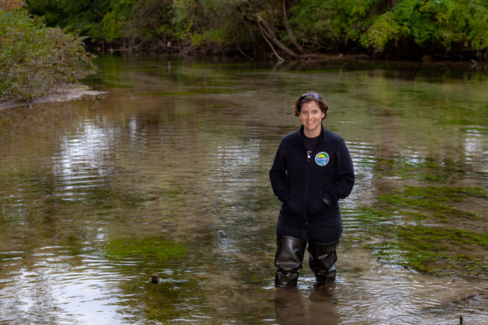 Julie Vastine stands in stream.