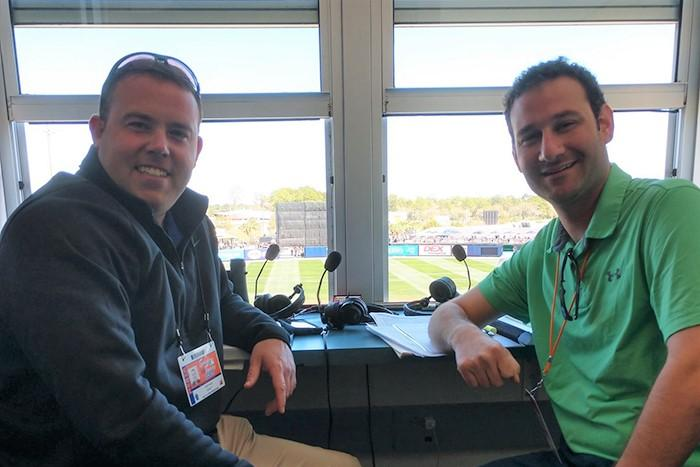 Photo of Geoff Arnold and Brett Hollander inside the Orioles broadcasting booth.