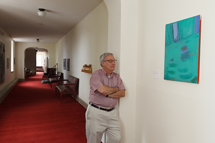 Neil Weissman, provost and dean of the college, poses by a favorite work in the provost's art collection, displayed in Old West. Photo by Carl Socolow '77.