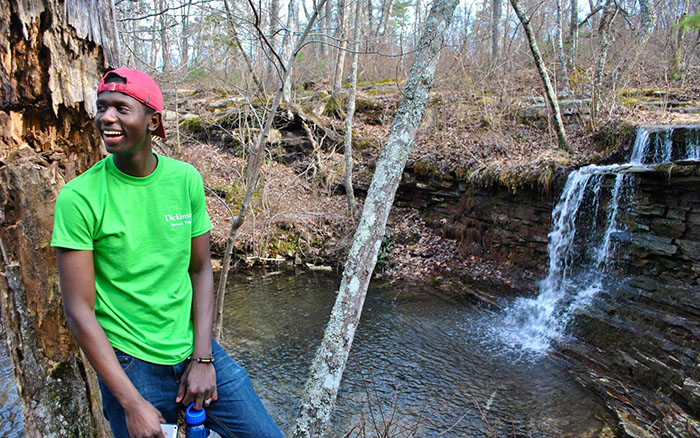 Mamadou Balde '16 smiles while leaning against a tree in front of a waterfall. Photo by Solai Sanchez '15.