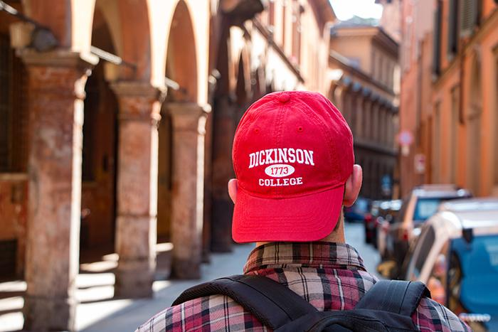 Photo of a young man wearing a Dickinson College baseball cap, walking down a street in a European city.