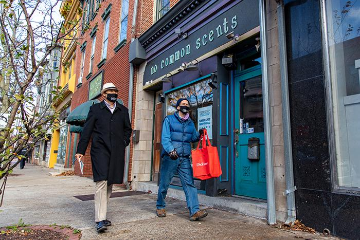 Photo of two men walking on the sidewalk in front of a store.