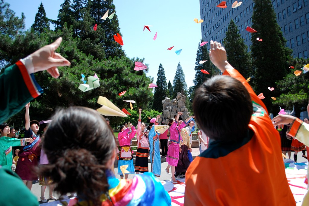 Students throwing paper planes in China during the 2008 summer program.
