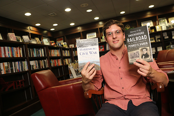 cooper wingert holds up two of his most recent books.