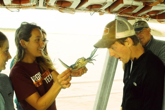 Picture of student holding crab on Chesapeake Bay