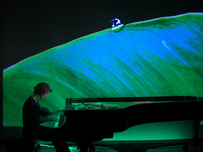 PIanist Jennifer Blyth, professor of music, performs as a video installation by Todd Arsenault, associate professor of art, is projected onstage.
