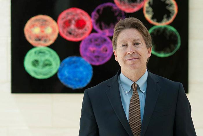 Portrait of Dale Bredesen in front of a visualization of cells.