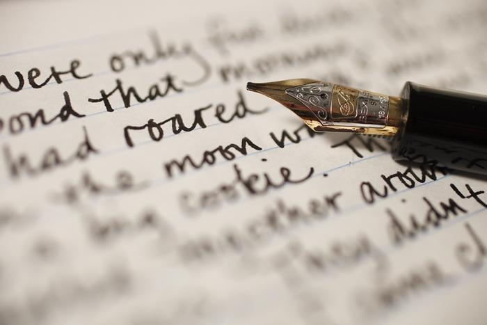 A pen rests on a manuscript