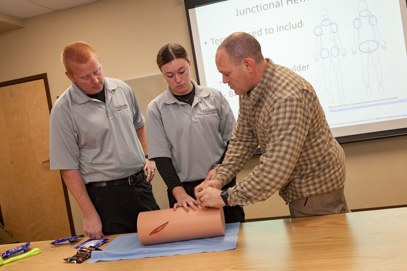 Military Science Instructor John Haiduck (right) instructs two Dickinson Public Safety officers on wound-packing technique during a recent training session for local first responders.
