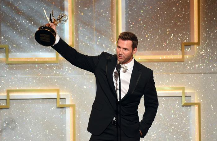 eric martsolf raises his Daytime Emmy award.