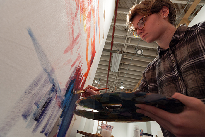 Sammy Holden '18 (art & art history, political science) works on a new painting in the Goodyear Gallery.