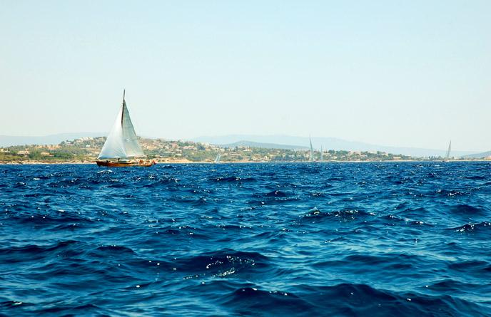Image of a sailboat in the water off the coast of Greece.