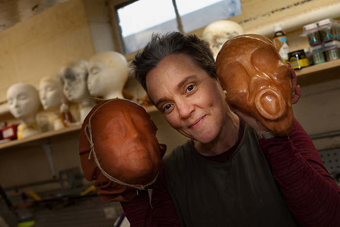 Professor of Theatre Sherry Harper-McCombs poses with masks-in-progress during a sabbatical focused on maskmaking and puppetry. Photo by Carl Socolow '77.
