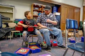 student teaching kid to play guitar