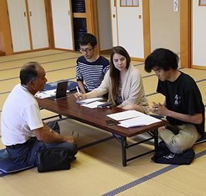 Students interviewing an older gentleman in Japan