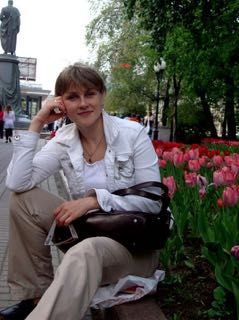 On-site Dickinson-in-Moscow director Irina Filippova, sits in front of a flower bed.