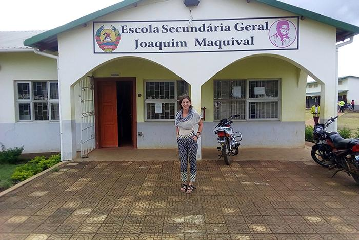 Photo of Dickinson alumni Jacqueline Shore in front of a small, white school building in Mozambique.