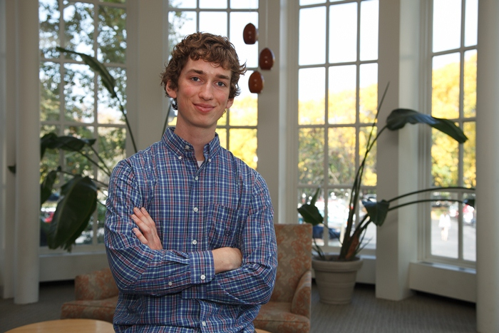 Alex Kasznel poses in the library.