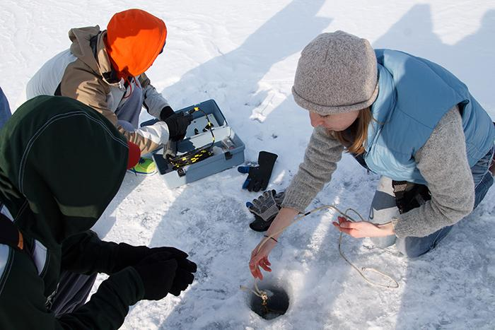 Assistant Professor of Environmental Studies Kristin Strock shows students how to take lake samples through ice to determine the impact of temperature on aquatic ecosystems.
