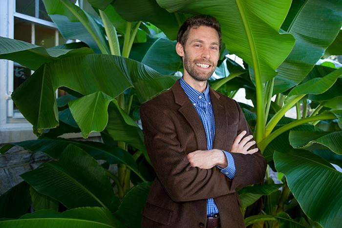 Associate Professor of Philosophy Chauncey Maher smiles under shiny, green banana leaves growing outside East College.