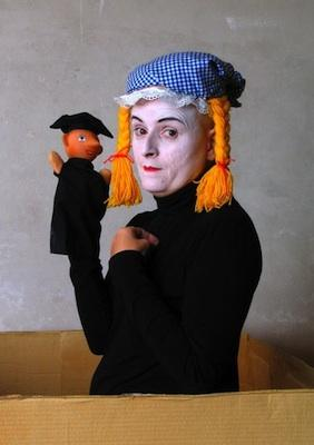 Performer Bridge Markland in costume holding a puppet.