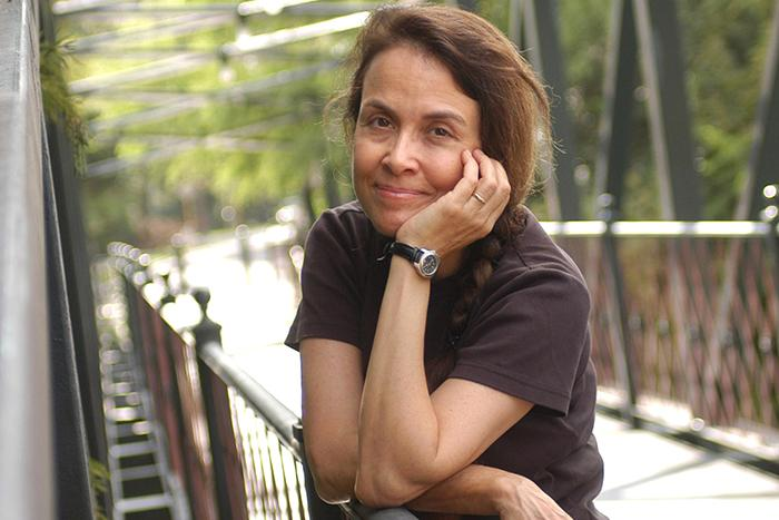 Photograph of Naomi Shihab Nye standing on a bridge.