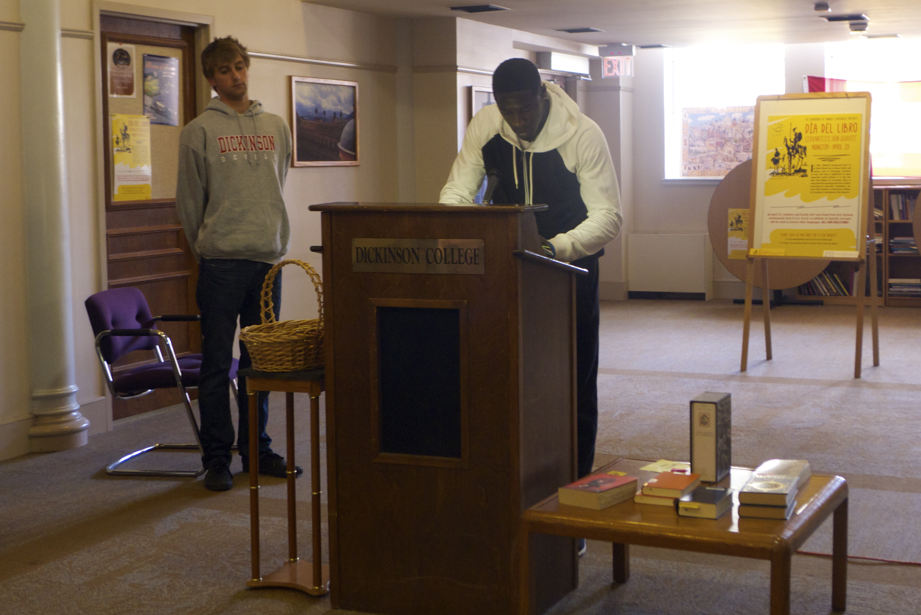 A student reads from Don Quixote in the Biblio Café while another student stands by for his turn at the podium.