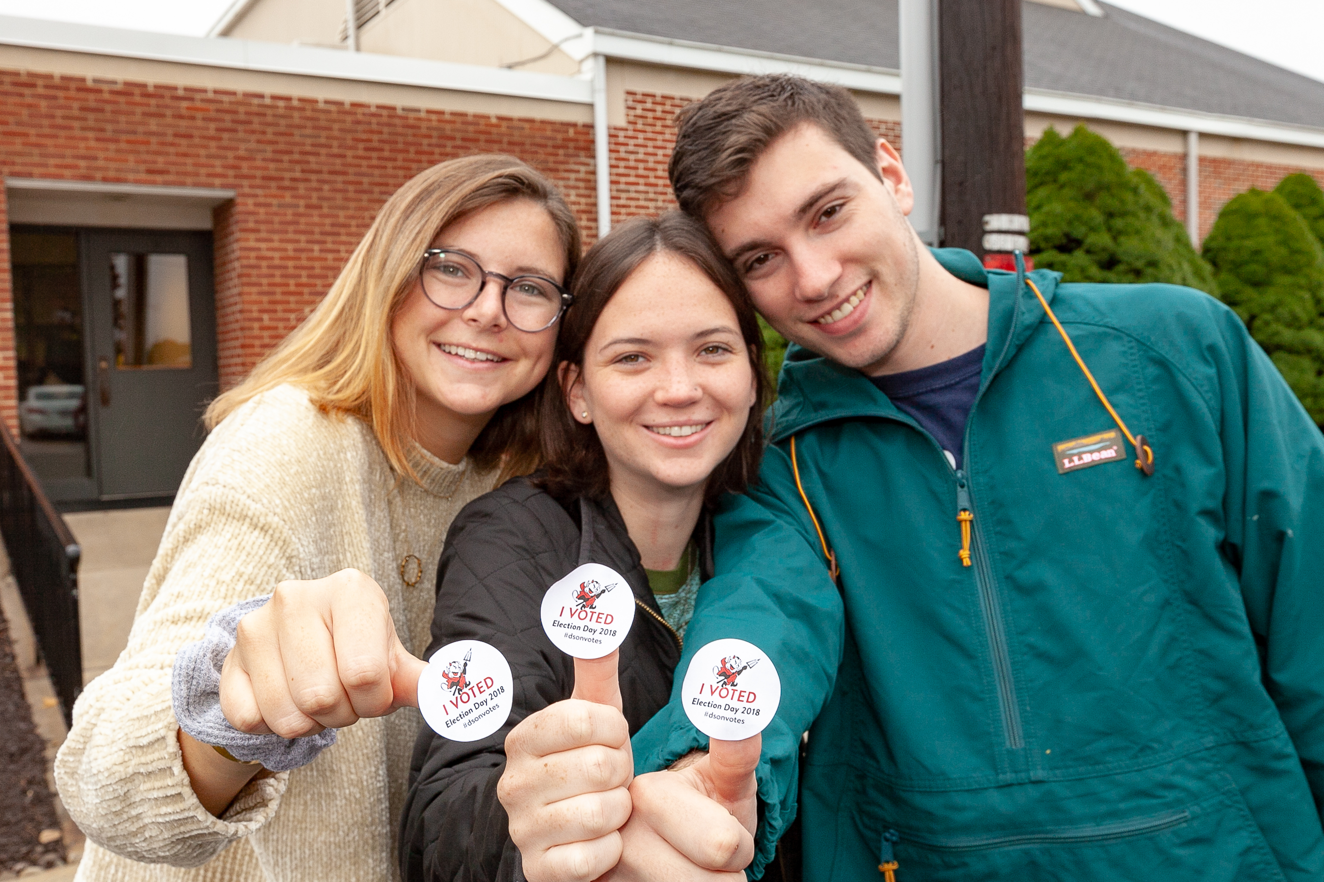 Three students displaying their I Voted stickers.