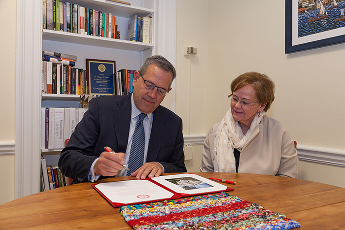 Doug Pauls '80 signs an agreement to support the internship fund, as President Margee Ensign looks on. Pauls and wife Terri will match any internship-fund gift, up to $100,000. Photo by Carl Socolow '77.