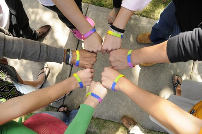 Hands in a circle showing pride bands.