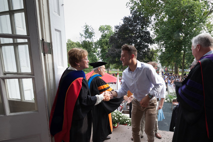 President Margee Ensign greets students as they climb the steps to Old West to officially sign in to the college.