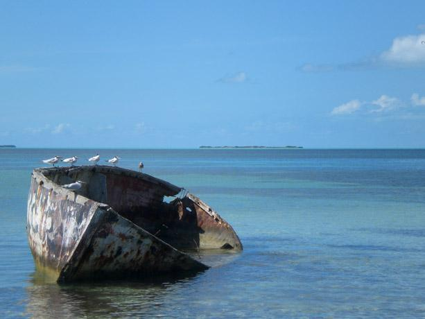 A boat resting in the water off of a Caribbean island.