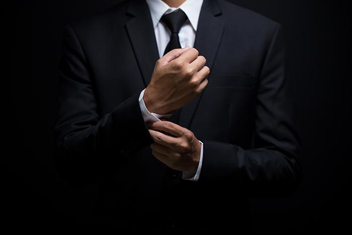Photo of a man in a business suit adjusting his cufflinks.