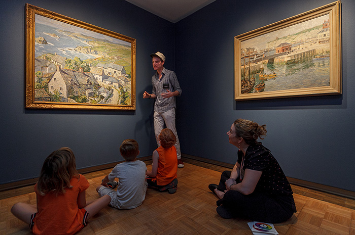 Taylor Hunkins '17 introduces local children to basic art-appreciation concepts during a June 30 community presentation in The Trout Gallery, while Curator of Education Heather Flaherty looks on. Photo by Carl Socolow '77.