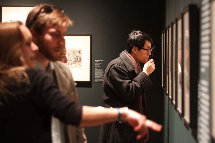 Students examine the finely detailed prints featured in the student-curated exhibition Letters and Lines. Photo by Carl Socolow '77.