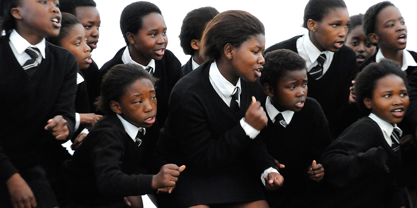 South African girls in school uniforms dancing and singing.