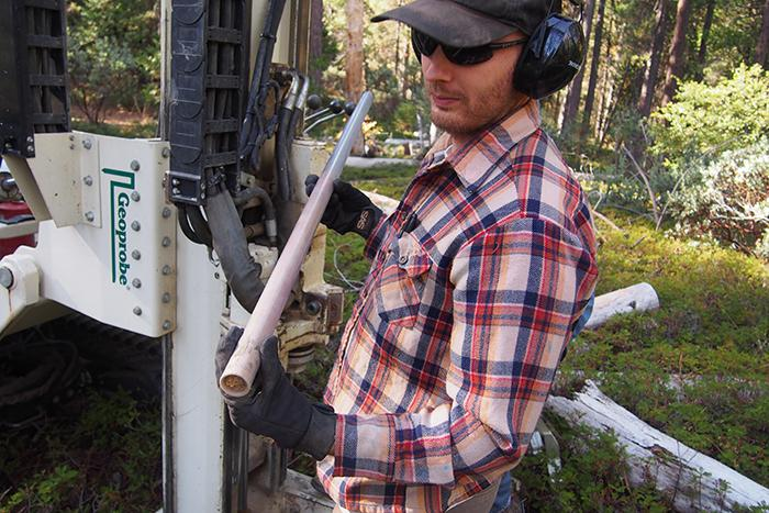 Photo of a man in a plaid shirt holding a tube containing a rock sample.