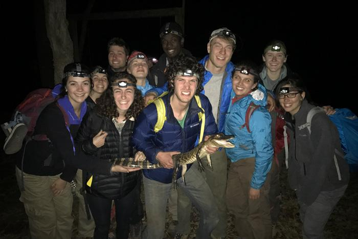 Students with an alligator at night
