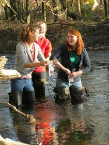 Students getting bacteria samples from a creek.