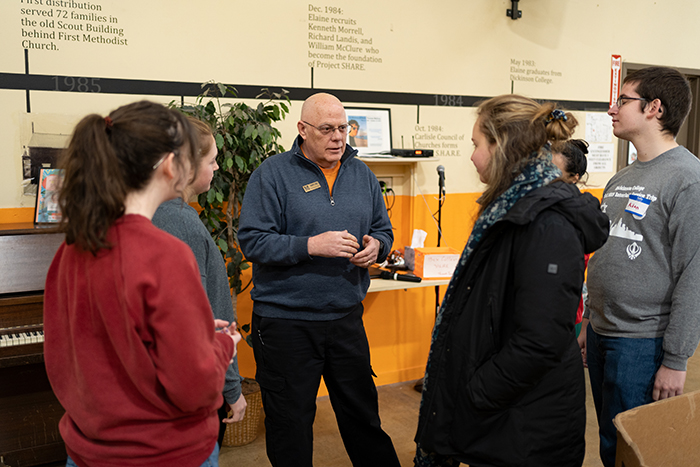 Bob Weed '80 speaks with student volunteers at the Project SHARE food bank. Photo by Joe O'Neill.
