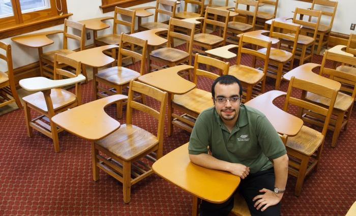 Gilbert Bonafe sits in a classroom, surrounded by desks.
