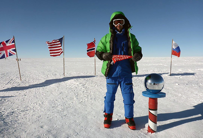 Cameron Kerr '09, a veteran and amputee, displays a Dickinson banner at the South Pole's Amundsen-Scott Research Station.