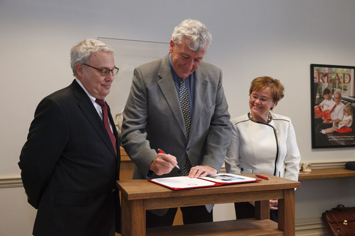 Jim Chambers '78 signs the agreement for his $1 million gift to Dickinson as interim President Neil Weissman and President-elect Margee Ensign look on.