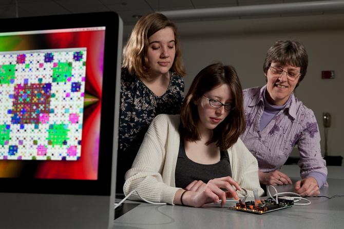 Three female scientists test out a computer science project.