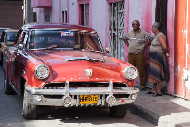 Two people standing next to a car on a Cuban street.