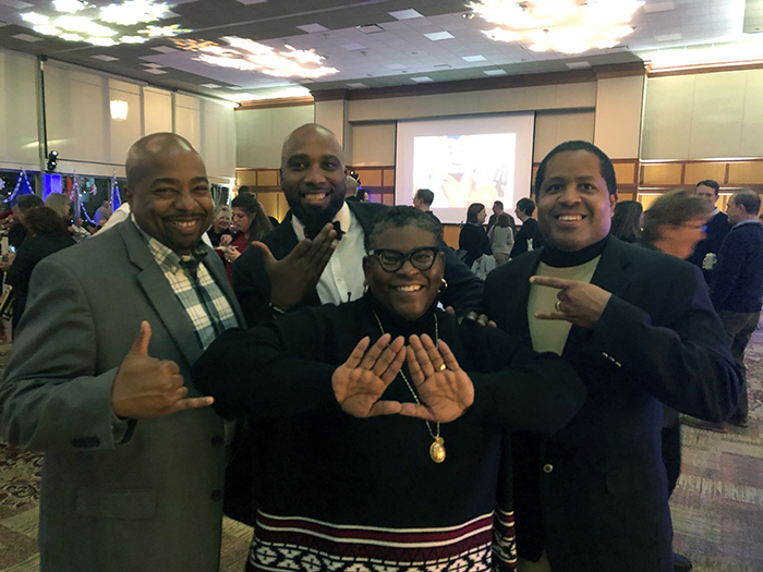 Displaying the hand symbols of their historically Black Greek organizations are: Dickinson leaders George Stroud (far left), Bronte Burleigh-Jones (center) and Kendall Isaac (far right) and Alan Paynter P'24.